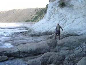 Andrew climbing along beach at Kaikoura Peninsula, New Zealand
