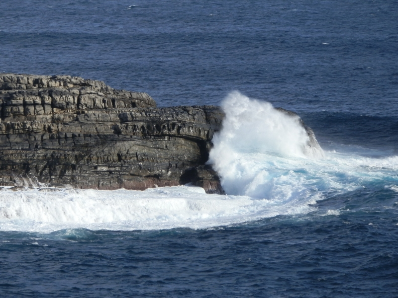 waves splashing up and over one of the Casaurina Islets at Cape du Couedic